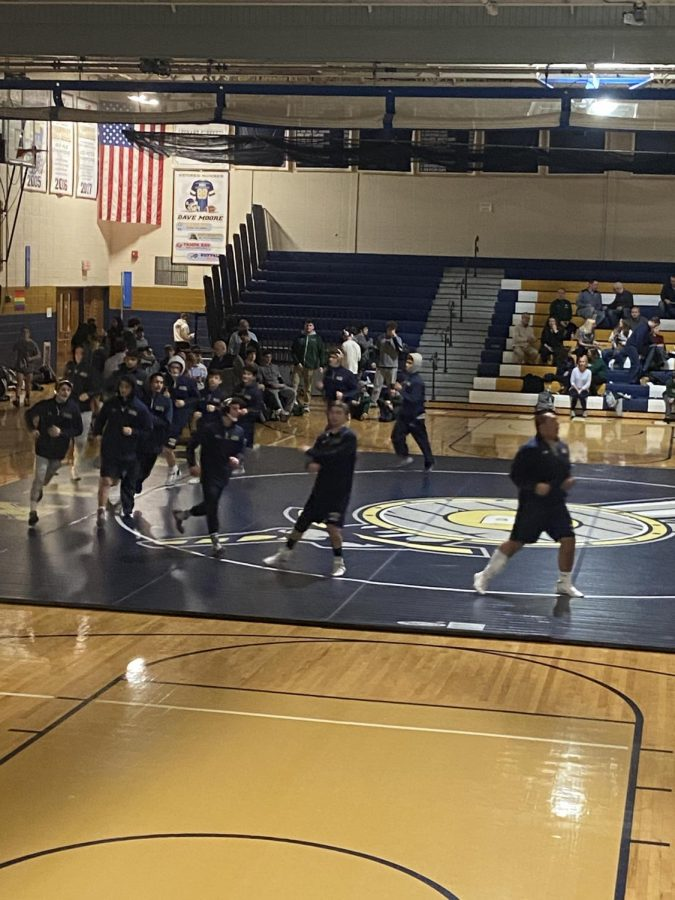 Roxbury High School's Wrestling Team is led by Senior Charles Lisa as they jog a loop on the mat in front of their home fans before a big match against Delbarton.